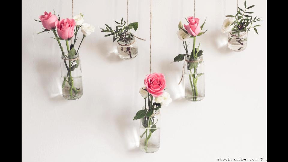 Upcycling im Trend Rosen an einer Wand in Flaschen als Wanddeko